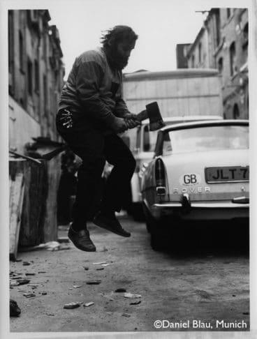 Portrait A.R. Penck sitzend auf einer Axt und sprint in die Luft